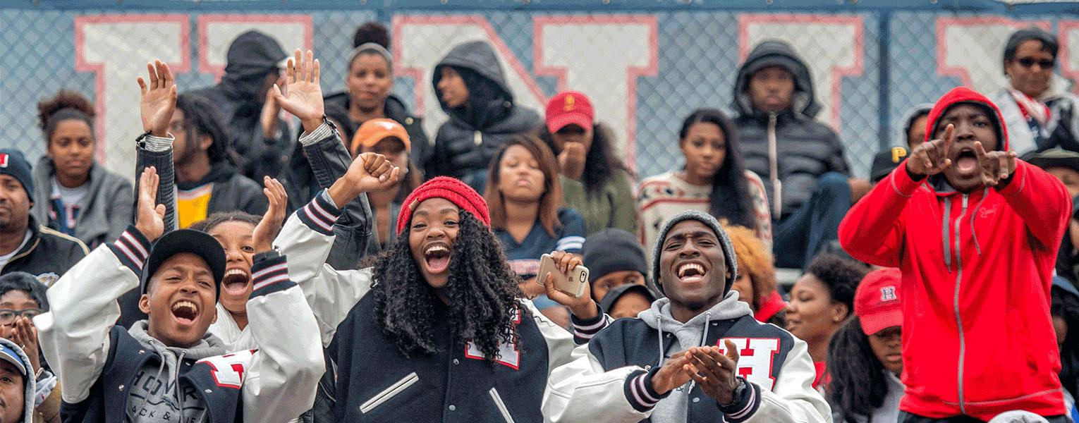 A large, diverse group of cheering students on bleachers at Howard Homecoming.